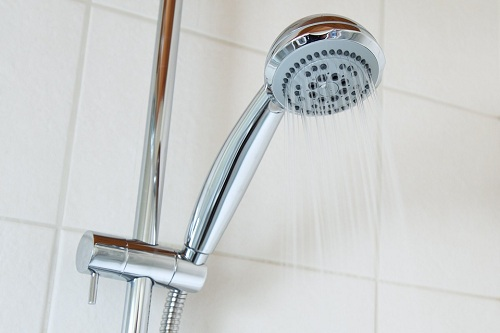 silver shower head with water splashing on it
