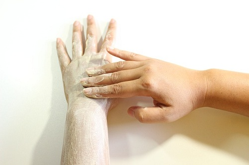 a persons applying body scrub on her hands